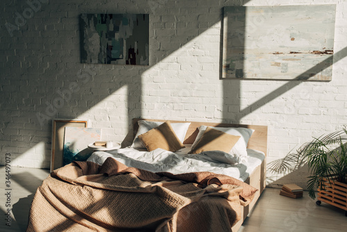 Fotografia bedroom interior with bed, pillows and paintings in sunlight with shadows