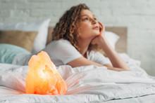 Thoughtful Girl Lying On Bed With Himalayan Salt Lamp, Selective Focus