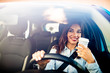 Portrait of a young and cheerful woman with coffee cup driving luxury car in the city. Smiling pretty young woman drinking take out coffee when driving to work in the morning