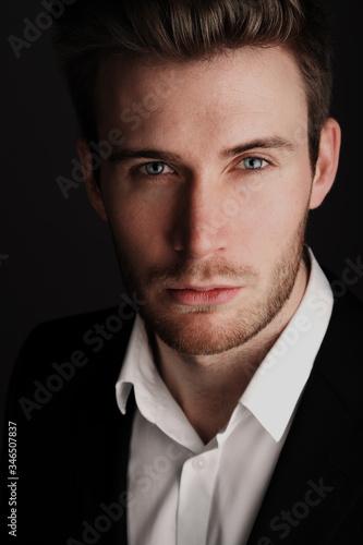 Portrait eines jungen Mannes im Anzug vor schwarzen Hintergrund. Fotobehang