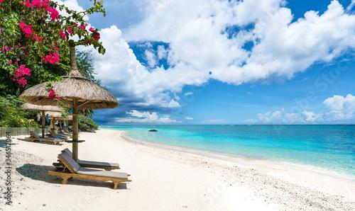 Fotografie, Obraz Public beach with lounge chairs and umbrellas in Pointe aux Canonniers, Mauritiu