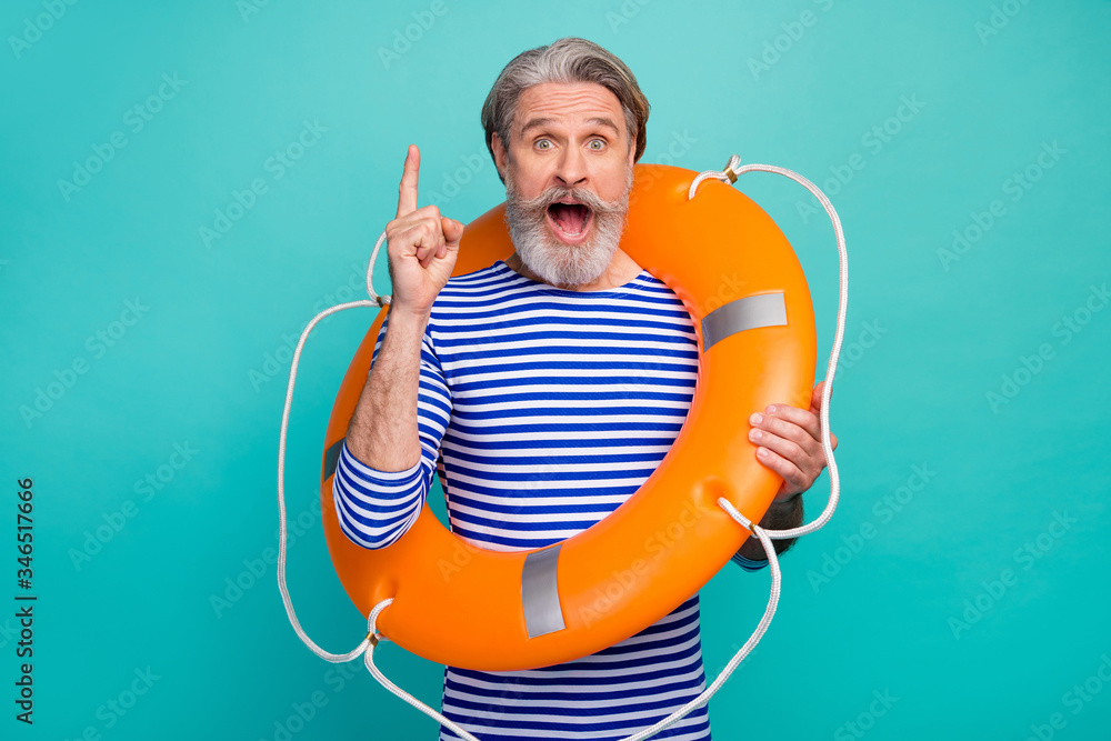 Fototapeta Photo of attractive aged seaman raise index finger genius orange security saving life buoy ship boat trip voyage wear striped sailor shirt white isolated teal color background