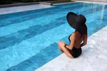 Attractive Slim Woman Sitting  Near The Pool In The Black Swimsuit. Pretty Unrecognizable Woman In The Black Hat Sitting The Back Side To Camera.