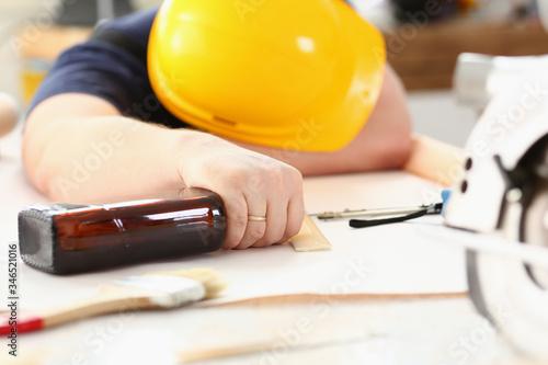 Arm of drunken worker in yellow helmet hold liquor Fototapeta
