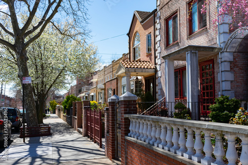 Photo Row of Beautiful Homes along a Sidewalk during Spring in Astoria Queens New York