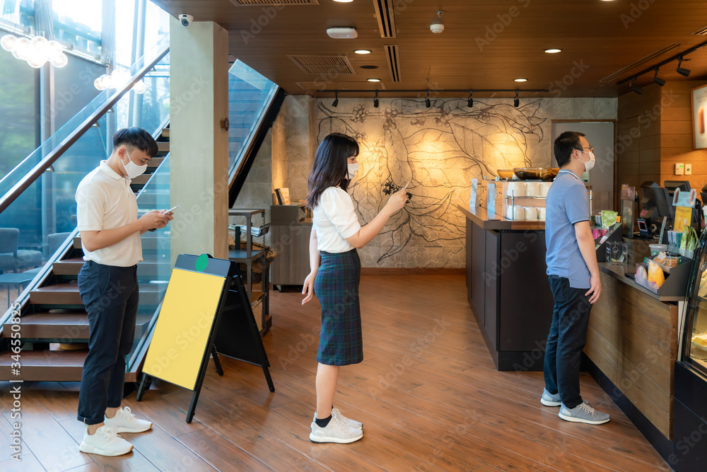 Fototapeta Three Asian people wearing mask standing distance of 6 feet from other people keep distance protect from COVID-19 viruses and people social distancing for infection risk at coffee cafe..
