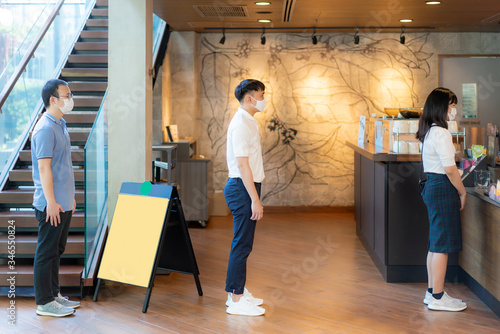 Obraz na plátně Three Asian people wearing mask standing distance of 6 feet from other people keep distance protect from COVID-19 viruses and people social distancing for infection risk at coffee cafe