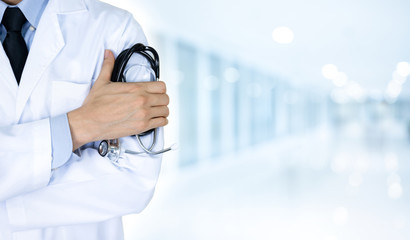 Man doctor holding stethoscope at hospital on blur blue background with copy space, health care concep