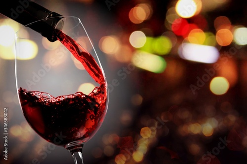Fotografia Red wine pouring from the bottle in glass