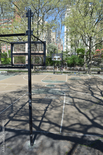 Photo Two basketball backboards with no hoops and no nets in an empty court in a public park on a sunny day with empty park benches, May 6, 2020, in New York