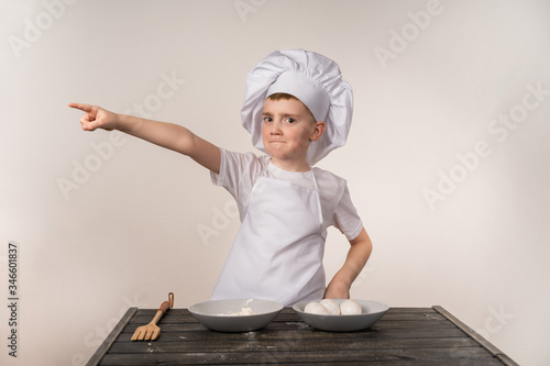 A cute little boy in a chef's costume cooks food with emotions little commander Fotobehang