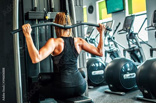 Naklejka premium Kobieta trenująca na siłowni, mięśnie pleców.