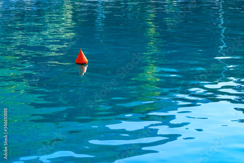 Fototapeta An orange buoy sways on the turquoise sea waves of the Gulf of Corinth