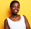 Beautiful happy young african woman isolated over yellow background