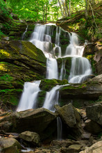 Mountain Waterfall In A Green Forest Among Stones And Trees. Cascade Falls Over Mossy Rocks