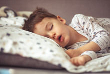 Lovely Face Expression With Open Mouth Of Blonde Caucasian Three Years Old Child, Sleeping On King Bed. Sweet Dreams. Little Baby Boy Sleeping While Lying On Couch At Home