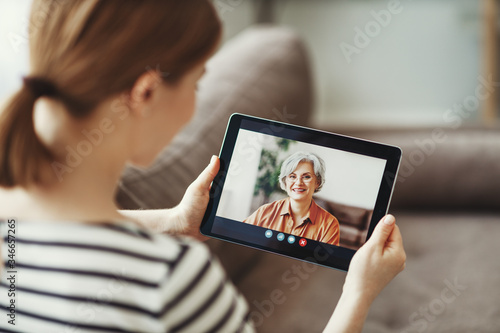 Obraz Young woman having video call with eldery mother on tablet - fototapety do salonu