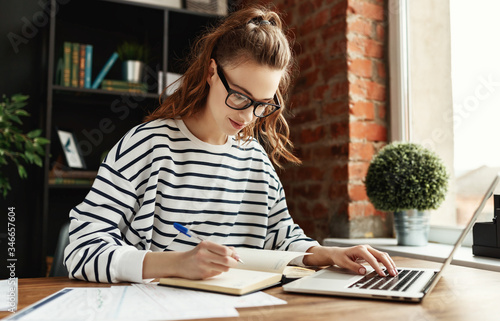 Happy millennial woman taking notes in notepad while working at laptop in comfortable loft office Fototapete