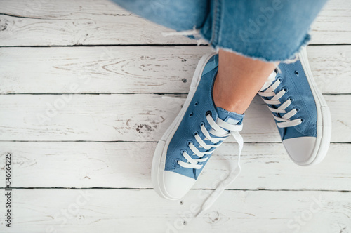 Fotografia Teenager's feet in casual blue new sneakers on the white wooden floor close up image