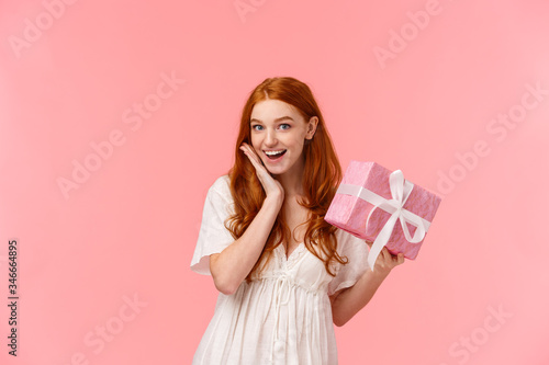 Photo Surprised, silly and lovely feminine redhead girl receive gift, look amused and