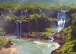 Iguazu waterfalls in Argentina, view from Devil's Mouth. Panoramic view of many majestic powerful water cascades with mist and splashes. Panoramic image of Iguazu valley from above.