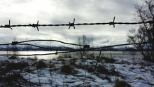Barbed Wire Fence Against Cloudy Sky