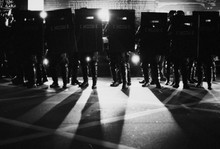 Police Force Standing With Riot Shield On Illuminated Street
