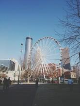 Ferris Wheel By Skyscraper In Skyview Atlanta Against Sky