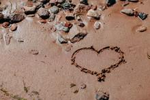 Ocean Shore, Sand And Rocks On The Sea Coast. Heart Drawing On Sandy Beach.