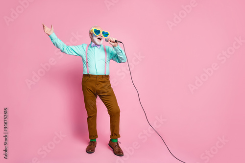Fototapeta Full size photo of funny stylish grandpa holding karaoke microphone singing party songs chilling wear cool specs shirt suspenders bow tie pants socks isolated pink pastel color background obraz