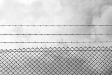 Low Angle View Of Barbed Wire Over Chainlink Fence Against Cloudy Sky
