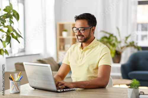 Obraz technology, remote job and lifestyle concept - happy indian man in glasses with laptop computer working at home office - fototapety do salonu