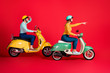 canvas print picture - Profile side view of her she his he nice attractive cheerful cheery couple tourists riding moped enjoying city tour pointing far away isolated on bright vivid shine vibrant red color background