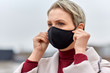 canvas print picture - health, safety and pandemic concept - young woman wearing black face protective reusable barrier mask outdoors
