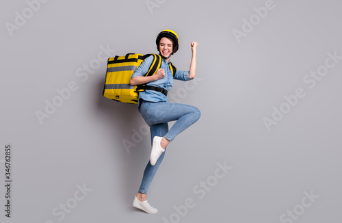 Fototapeta Full body photo crazy ecstatic girl courier deliver all quarantine covid-19 offer raise fists scream carry thermo container package wear denim jeans shirt helmet isolated gray color background obraz