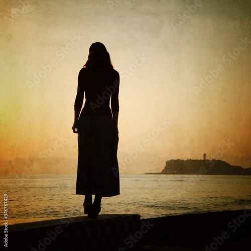 Obraz Rear View Of Silhouette Woman Standing On Retaining Wall By Sea - fototapety do salonu
