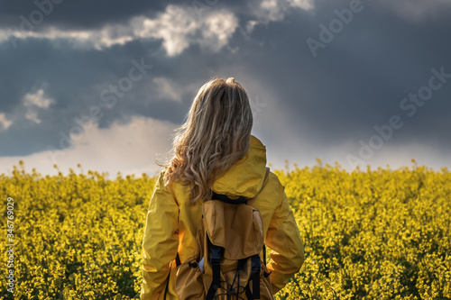Storm and rain is coming. Hiking woman standing in rapeseed field and looking at cloudy sky. Tourist wearing yellow waterproof jacket