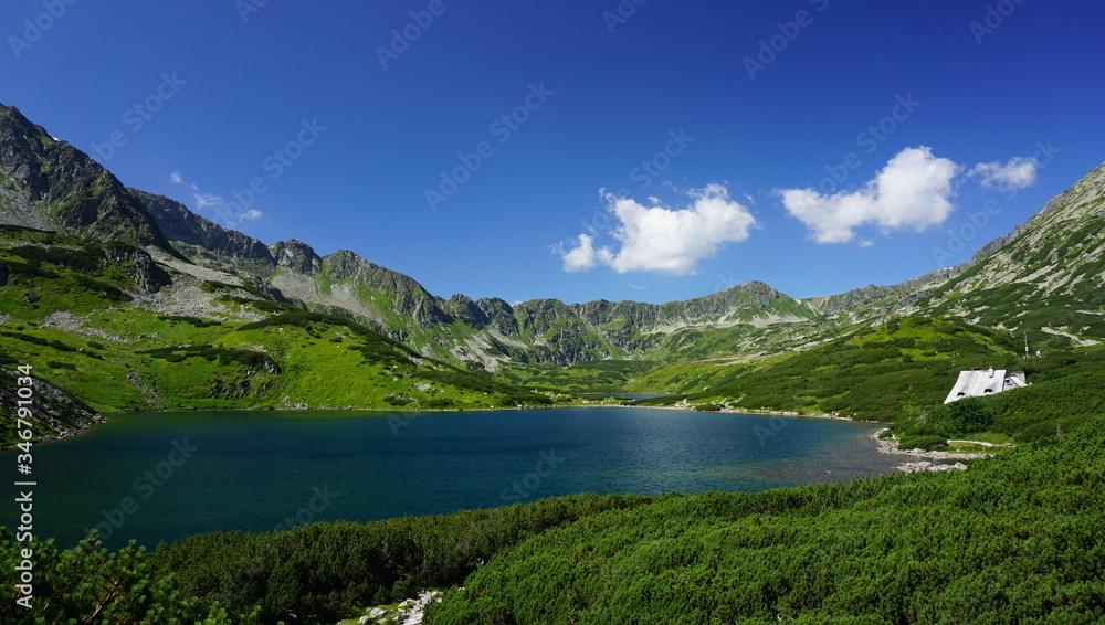 Fototapeta górski krajobraz ze stawem, błękitne niebo z białymi chmurami