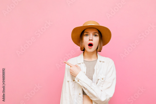 Fotografija Surprised pretty girl in light summer wears and hat isolated on pink background, looks in camera with emotionless face and points finger aside on empty space
