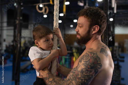 Photo Fit father teaching son to climb rope