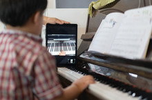 A Boy Is Learning Piano Online...