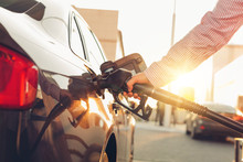 Man Handle Pumping Gasoline Fuel Nozzle To Refuel At Petrol Station. Transportation And Ownership Concept. Sunset Lighting