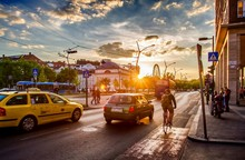 Cars And Bicycles Against Cloudy Sky In City During Sunset