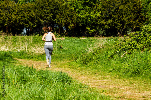 Fototapeta Woman jogging alone along a green path surrounded by hedges, brambles and other
