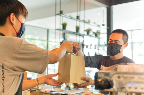 Fotomural Social distance conceptual waiter giving takeaway bag to customer at cafe