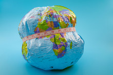 Global Obesity Epidemic Crisis Affecting Increasing Numbers Of Earth Population And Chronic Health Condition Concept With Globe And Measuring Tape Isolated On Blue Background