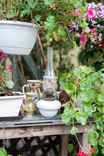 Vintage oil lamp and folk art jugs in the garden - pots of flowers on a table Tableau sur Toile