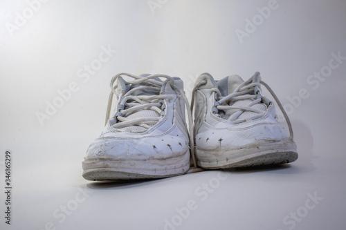 Zapatillas viejas blancas sobre un fondo blanco sentido del paso del tiempo, consistencia, etc Wallpaper Mural