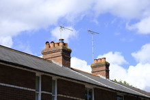 Two Isolated Chimney Stacks And Television Aerials In A British House Against A Blue Sky