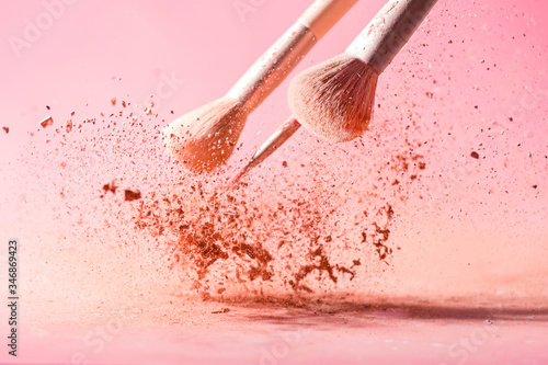Cuadros en Lienzo Make up brushes with powder splashes isolated on pink background